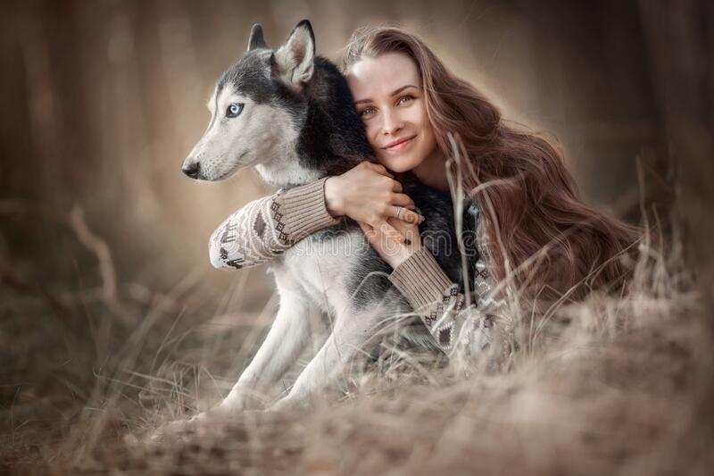 Portrait of a beautiful young woman with husky dog stock images