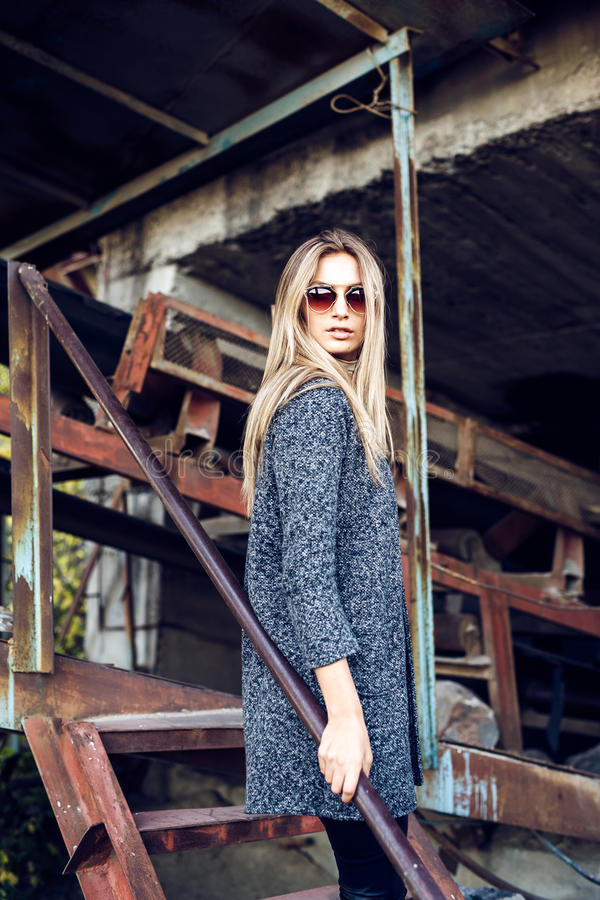 Portrait of a beautiful young woman in an industrial background. Portrait of a beautiful young blond womanin grey coat, sunglasses, leather pants in an royalty free stock photography