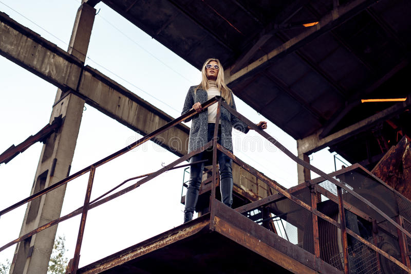 Portrait of a beautiful young woman in an industrial background. Portrait of a beautiful young blond womanin grey coat, sunglasses, leather pants in an royalty free stock photos