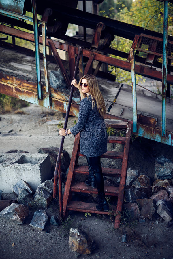 Portrait of a beautiful young woman in an industrial background. Portrait of a beautiful young blond womanin grey coat, sunglasses, leather pants in an stock photos
