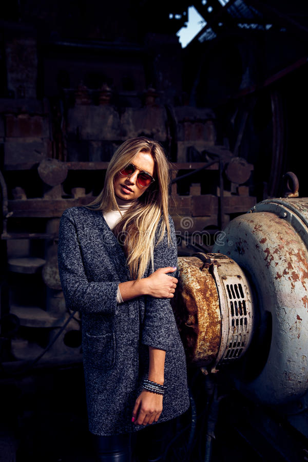 Portrait of a beautiful young woman in an industrial background. Portrait of a beautiful young blond womanin grey coat, sunglasses, leather pants in an royalty free stock photo