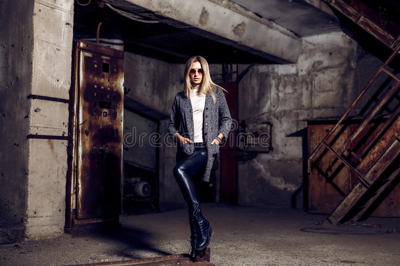 Portrait of a beautiful young woman in an industrial background. Portrait of a beautiful young blond womanin grey coat, sunglasses, leather pants in an royalty free stock images