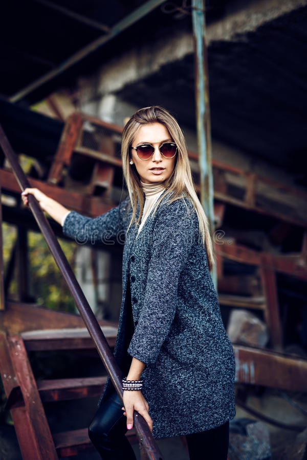 Portrait of a beautiful young woman in an industrial background. Portrait of a beautiful young blond womanin grey coat, sunglasses, leather pants in an stock photo
