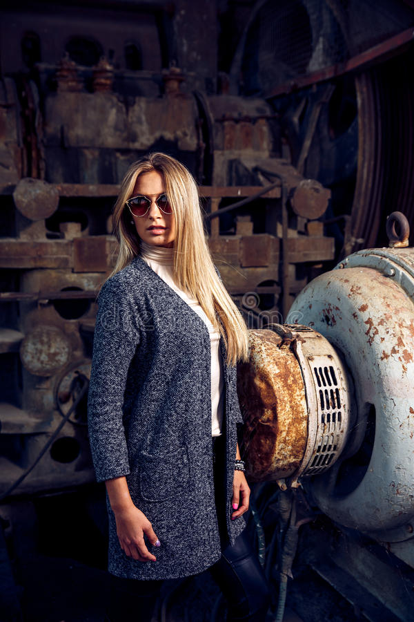 Portrait of a beautiful young woman in an industrial background. Portrait of a beautiful young blond womanin grey coat, sunglasses, leather pants in an royalty free stock image