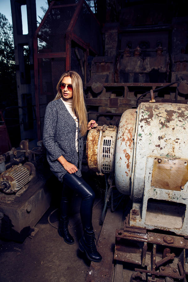 Portrait of a beautiful young woman in an industrial background. Portrait of a beautiful young blond womanin grey coat, sunglasses, leather pants in an stock photography