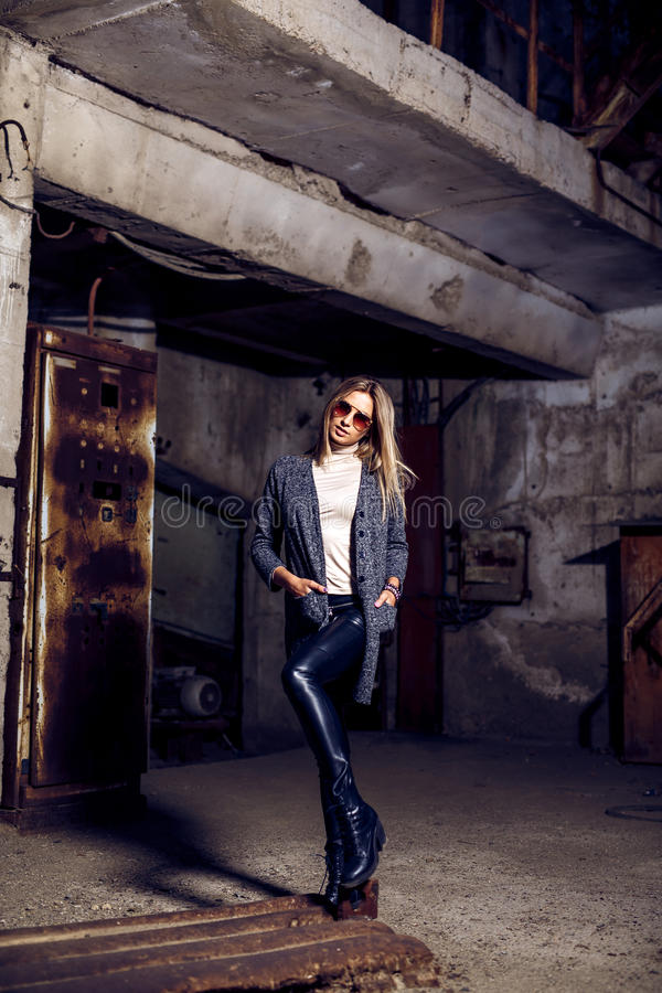 Portrait of a beautiful young woman in an industrial background. Portrait of a beautiful young blond womanin grey coat, sunglasses, leather pants in an stock image