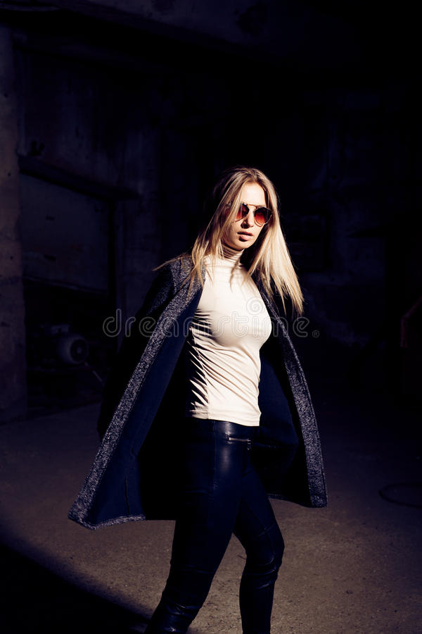 Portrait of a beautiful young woman in an industrial background. Portrait of a beautiful young blond womanin grey coat, sunglasses, leather pants in an stock images