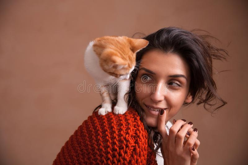 Portrait of the beautiful young woman with a kitten on the shoulder. Concept of loving animals, taking care and having fun with. Pets stock photography