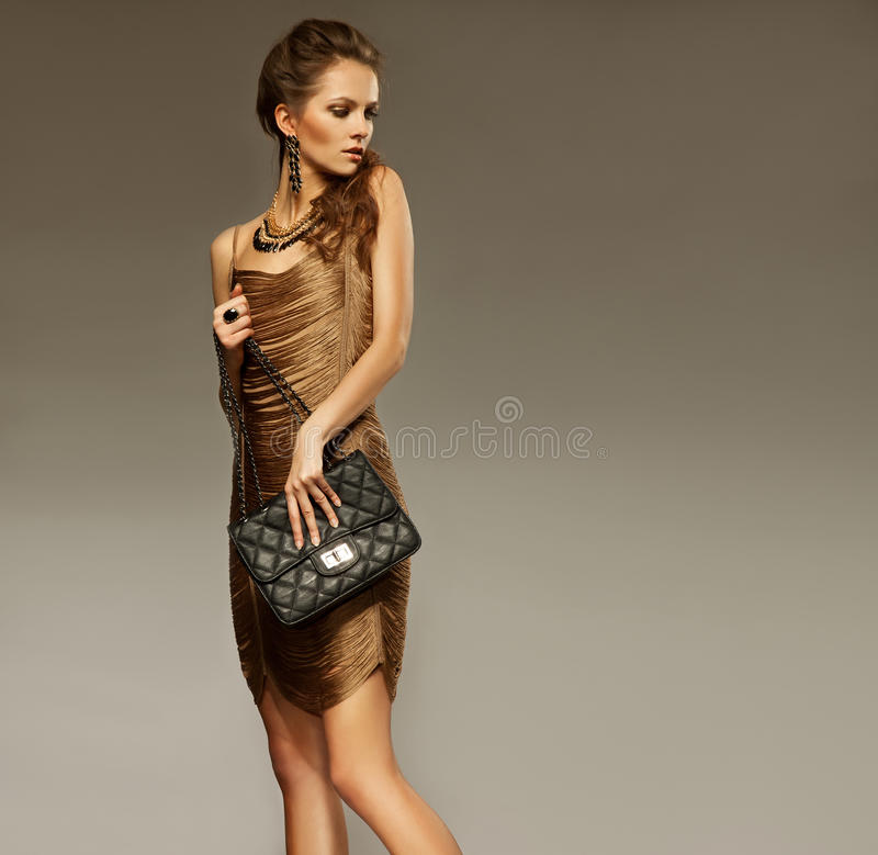 Portrait of beautiful young woman with a leather bag. Fashion ph royalty free stock photos
