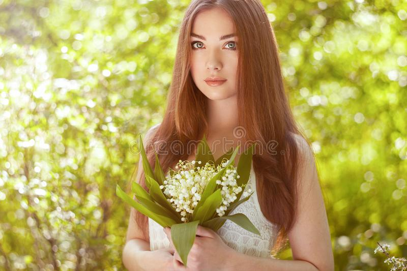 Portrait of beautiful young woman with lily of the valley. Girl on nature. Spring flowers. Fashion beauty stock images