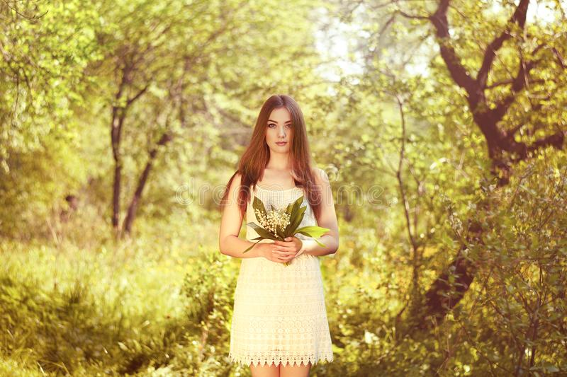 Portrait of beautiful young woman with lily of the valley. Girl on nature. Spring flowers. Fashion beauty royalty free stock images