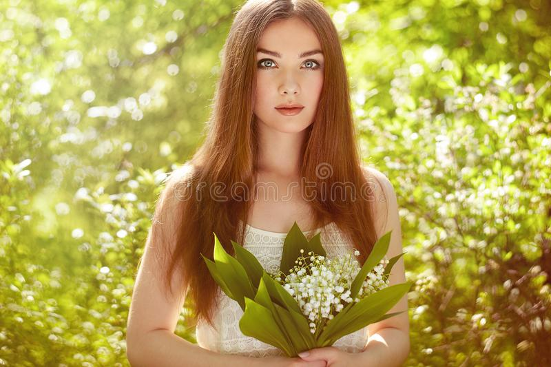 Portrait of beautiful young woman with lily of the valley. Girl on nature. Spring flowers. Fashion beauty stock image