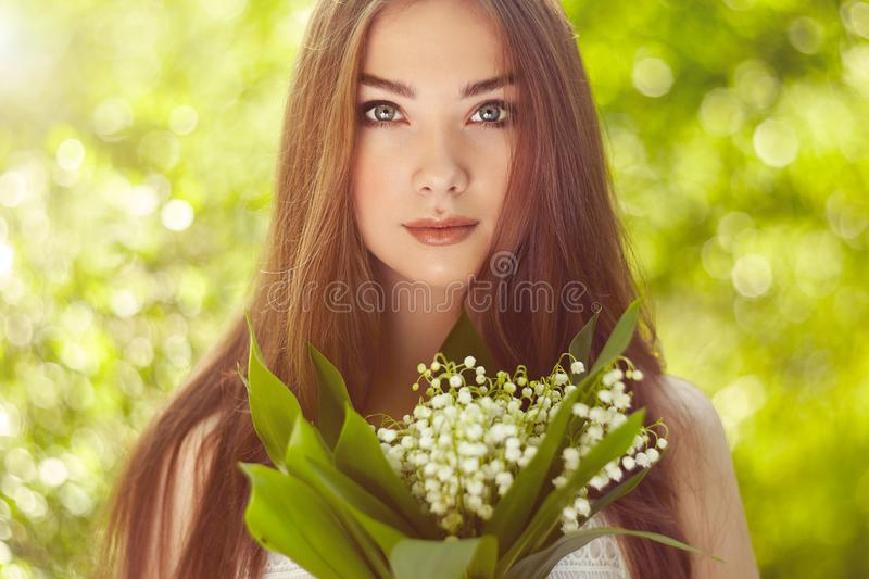 Portrait of beautiful young woman with lily of the valley. Girl on nature. Spring flowers. Fashion beauty royalty free stock photography