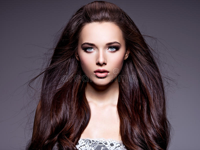 Portrait of the beautiful young woman with long brown hair. Posing at studio over dark background stock image