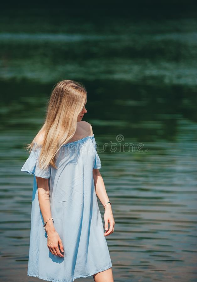 Portrait of beautiful young woman with long hair wearing blue dress standing near the lake shore on sunny summer day royalty free stock photo