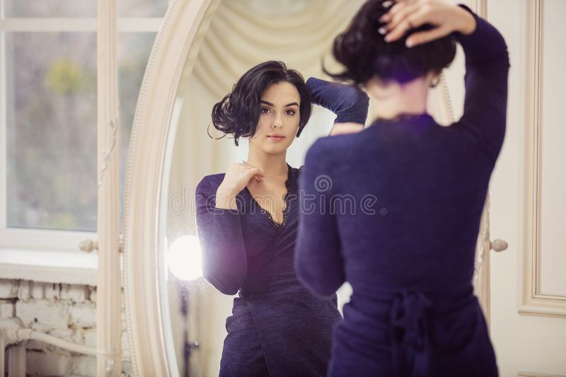 Beautiful young woman looking in mirror indoors stock photo