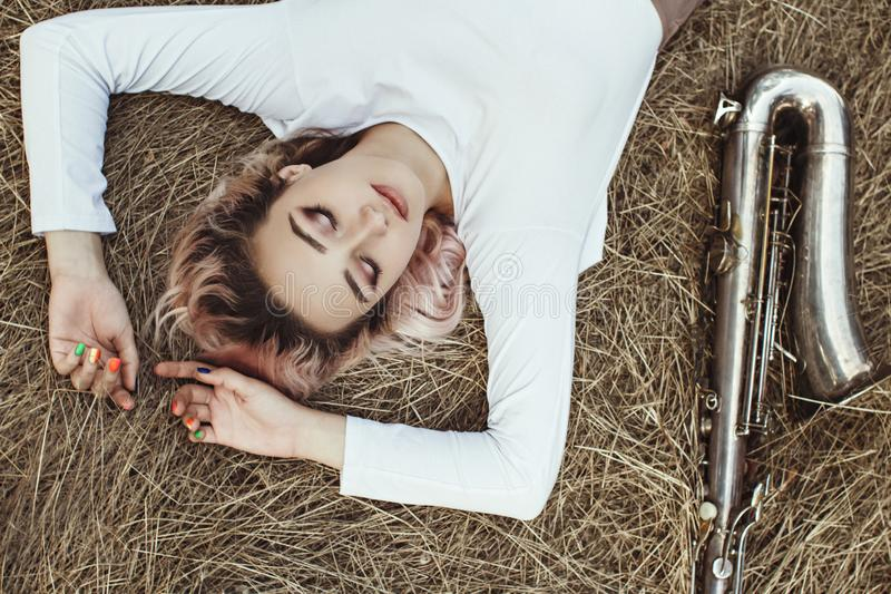 Portrait of a beautiful young woman lying on the dry grass next to the saxophone, face of blonde girl on the hay rests with a royalty free stock photo