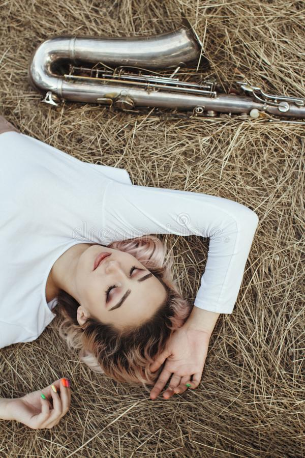 Portrait of a beautiful young woman lying on the dry grass next to the saxophone, face of blonde girl on the hay rests with a stock photo