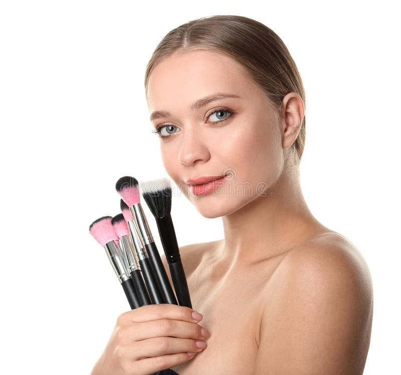 Portrait of beautiful young woman with makeup brushes royalty free stock photos