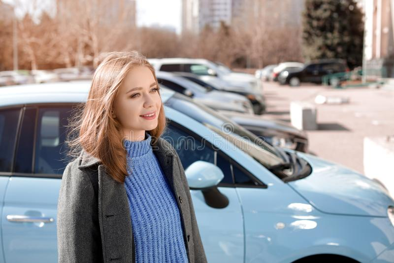 Portrait of beautiful young woman near parked cars. On sunny day stock photo