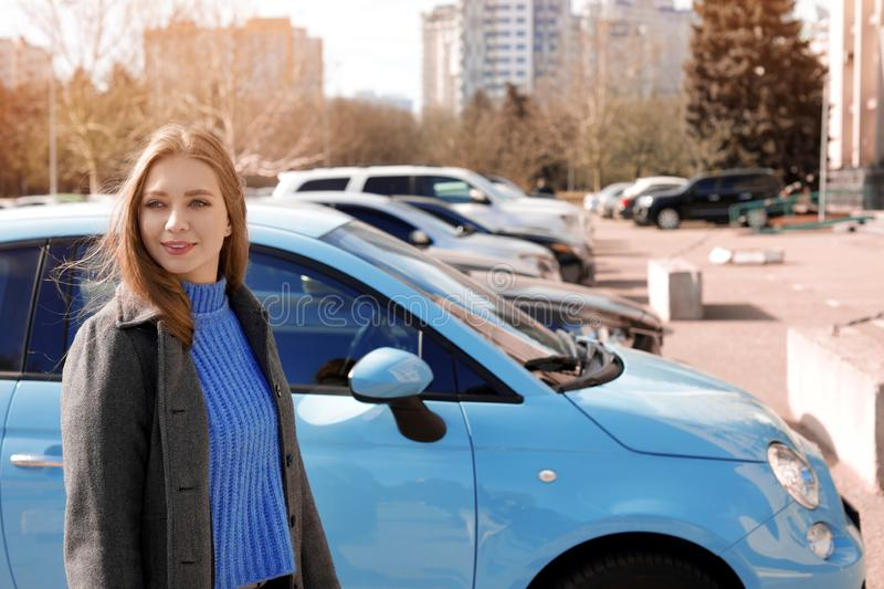 Portrait of beautiful young woman near parked cars. On sunny day royalty free stock images