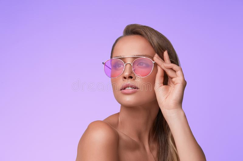 Portrait of beautiful young woman with perfect makeup wearing pink sunglasses. royalty free stock photography