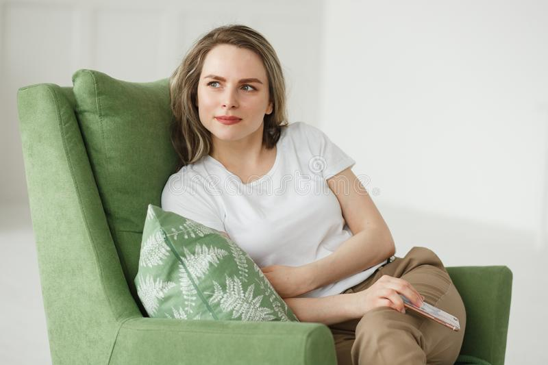 Portrait of beautiful young woman with phone sitting on armchair in light living room. stock photos