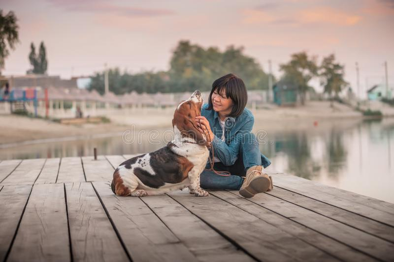 Happy woman playing with her dog by the river stock images