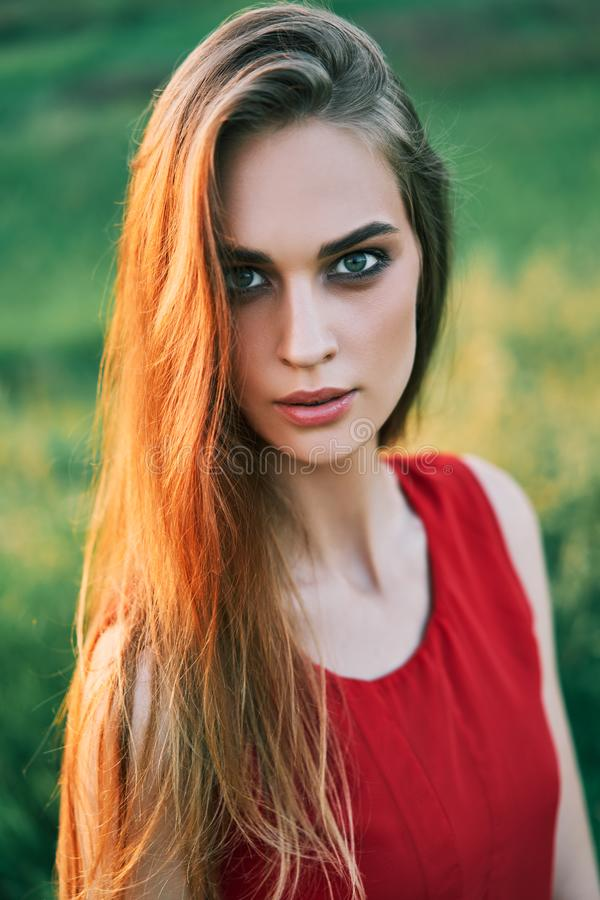 Portrait of beautiful young woman posing outdoors in summer sun stock photo