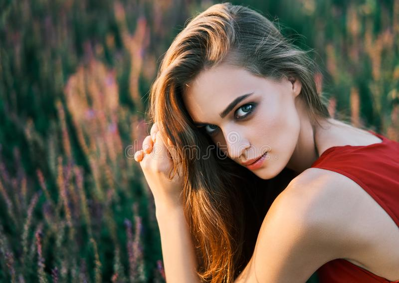 Portrait of beautiful young woman posing in sage field in summer sun stock photo