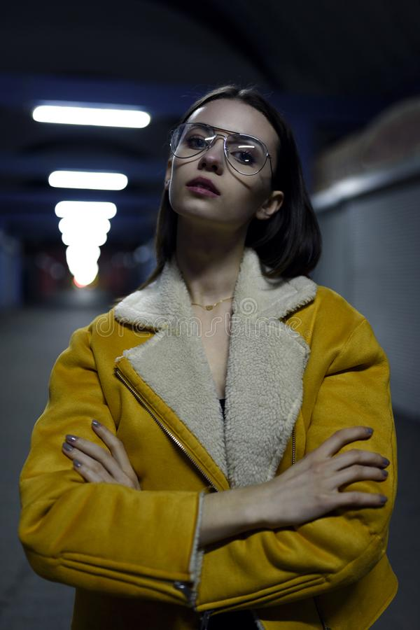 Portrait of beautiful woman posing in yellow jacket in city lights by night. Street fashion royalty free stock photos