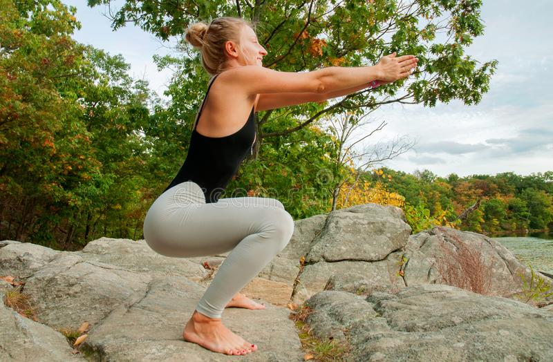 Portrait of beautiful young woman practicing yoga, squats exercises royalty free stock photo