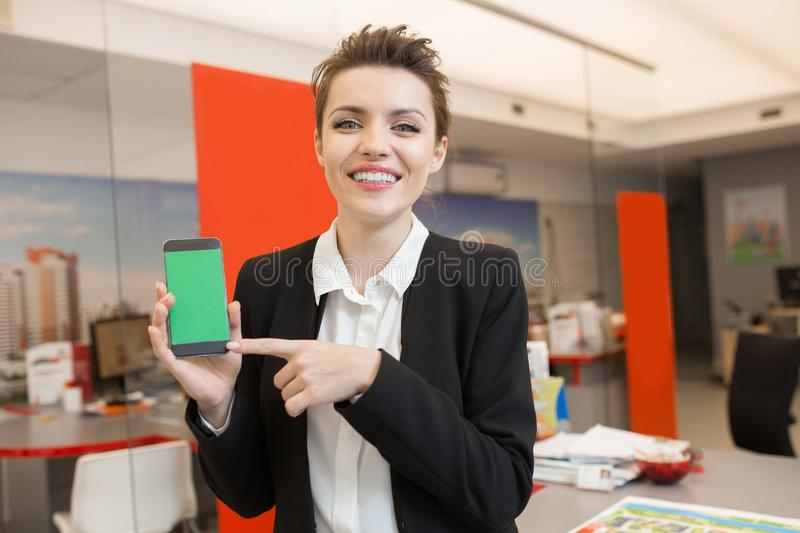 Woman Presenting Real Estate App. Portrait of beautiful young woman presenting mobile app and smiling happily at camera in real estate agency royalty free stock image