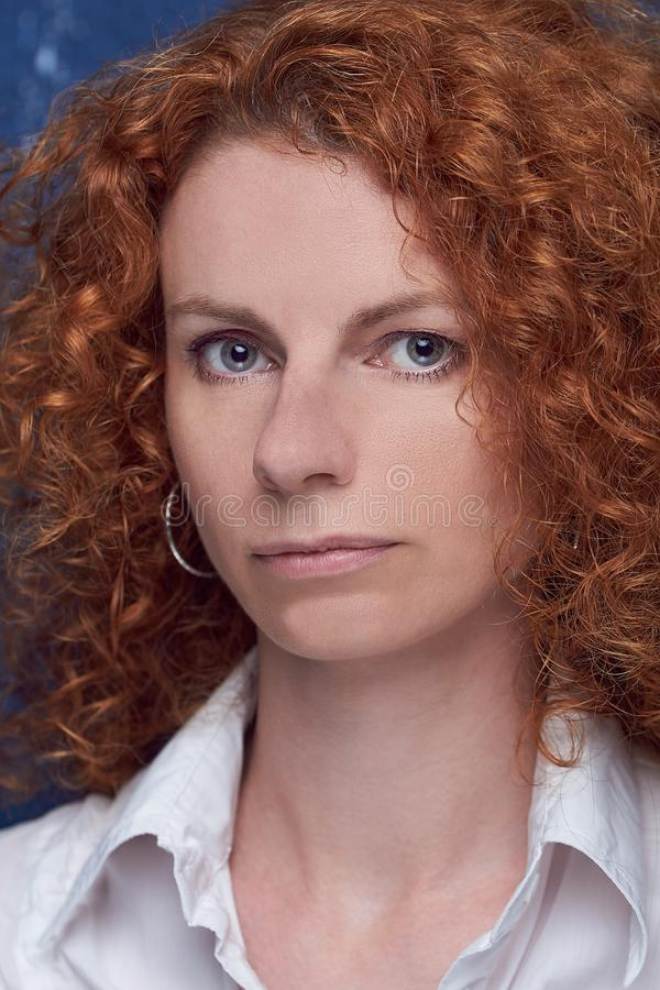 Portrait of beautiful young woman with red curly hair on blue background royalty free stock image