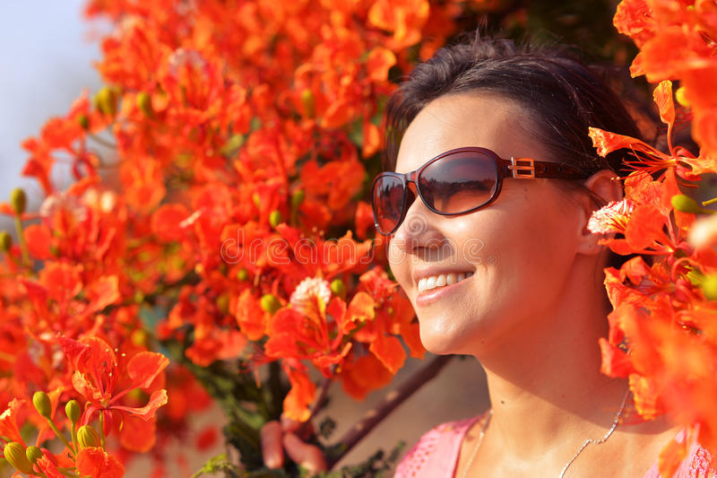 Portrait of beautiful young woman. In red flowers stock photography
