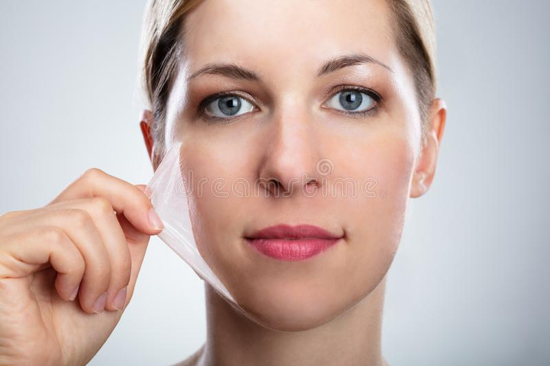 Woman Removing Peeling Mask From Her Face royalty free stock photos