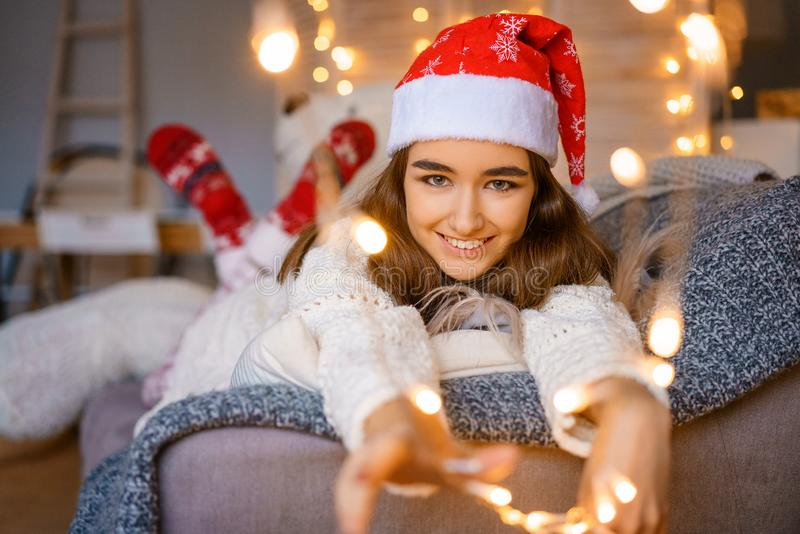 Portrait of beautiful young woman in Santa Claus hat on bokeh background royalty free stock photo