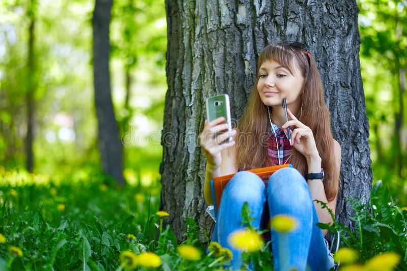 Portrait of a beautiful young woman selfie in the park with a smartphone.  stock photo