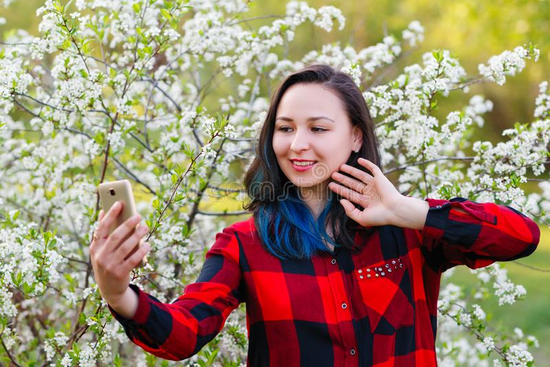 Portrait of a beautiful young woman selfie in the park with a smartphone doing stock photos