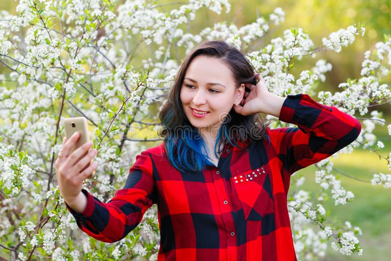 Portrait of a beautiful young woman selfie in the park with a smartphone royalty free stock photo
