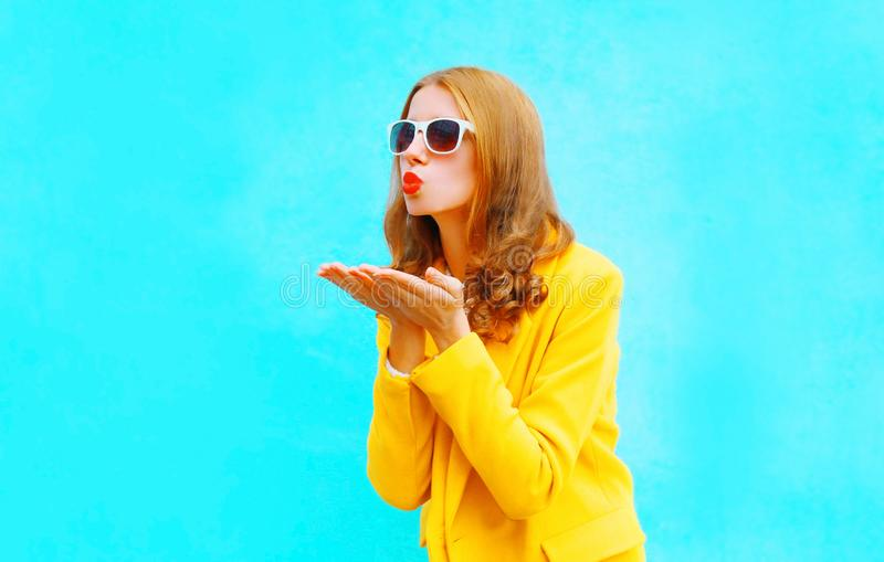 Portrait of beautiful young woman sends an air kiss in yellow coat stock images