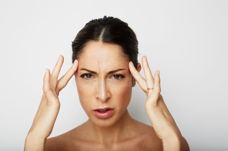 Portrait of Beautiful young woman with a severe headache with the hands in the head over white empty wall on background. Beauty and healthcare concept royalty free stock photo