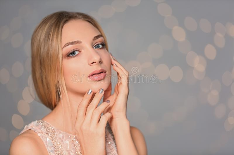 Portrait of beautiful young woman with shiny manicure on blurred background. Nail polish trends royalty free stock photos