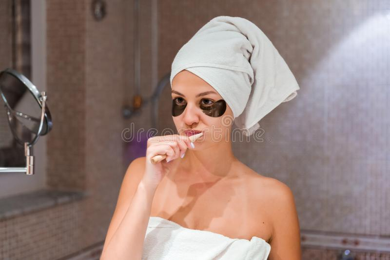 Portrait of a beautiful young woman after shower in patches. female brush teeth in front of her bathroom mirror. healty wellness stock images