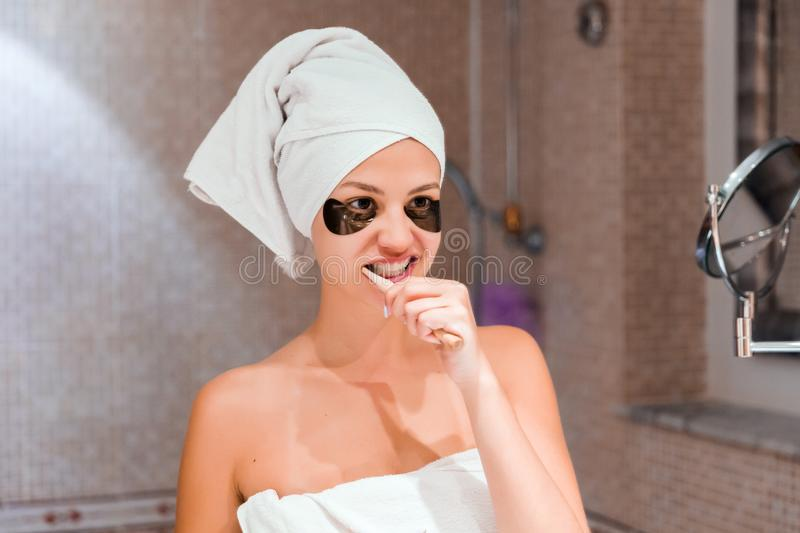 Portrait of a beautiful young woman after shower in patches. female brush teeth in front of her bathroom mirror. healty wellness. Morning concept royalty free stock photos