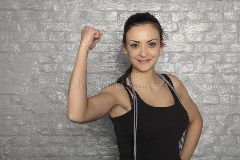 Portrait of a beautiful young woman showing biceps stock photo