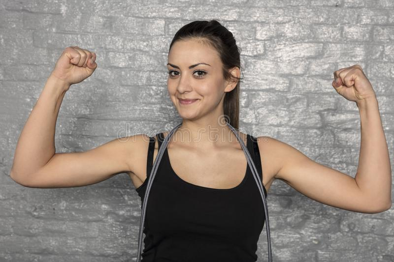 Portrait of a beautiful young woman showing her muscles royalty free stock image