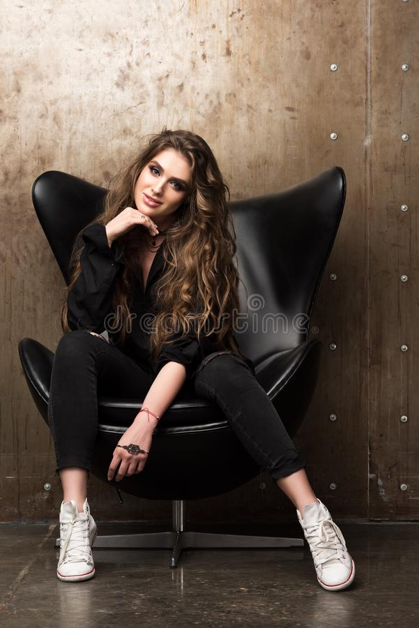 Portrait of beautiful young woman sitting in the black chair. Contemporary appearance. Black clothes and white sneakers. Long wavy hair. Back in the loft royalty free stock images