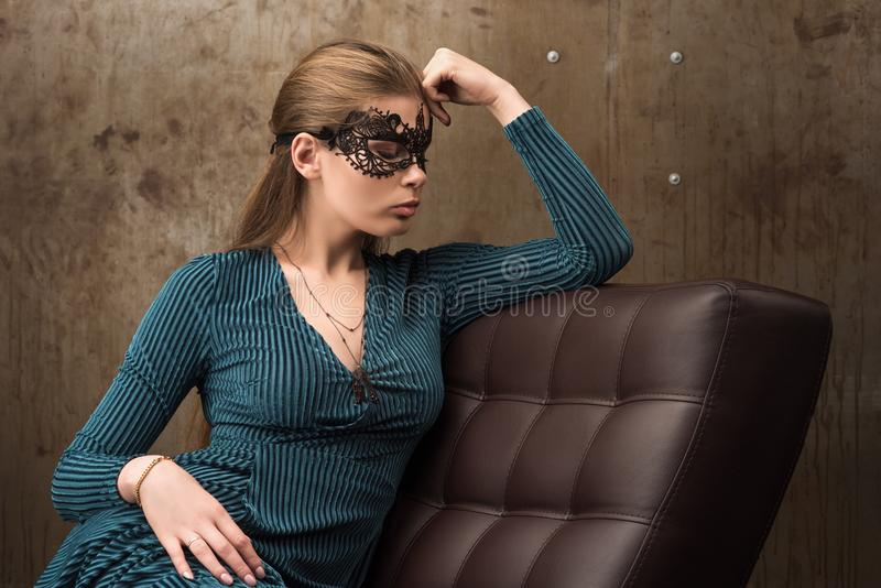 Portrait of beautiful young woman sitting on the couch. Black mask royalty free stock photography