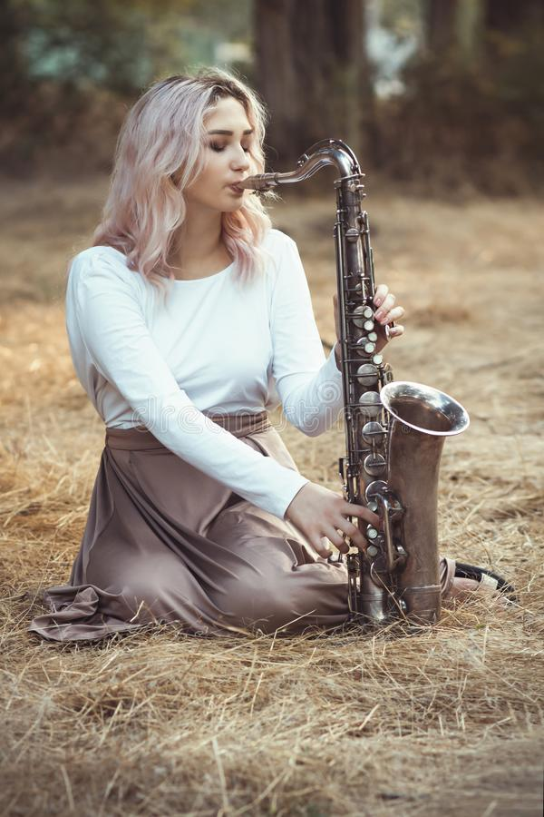 Portrait of a beautiful young woman sitting on the dry grass leanher head on saxophone, romantic blonde girl close eyes and royalty free stock photos